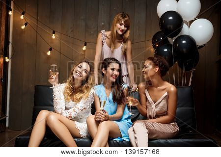 Four young beautiful girls in dresses speaking, laughing, drinking champagne, resting at party.