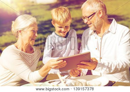 family, happiness, generation, home and people concept - happy family sitting at table with tablet pc computer outdoors