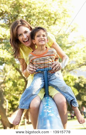 Mother And Son Riding On See Saw In Playground