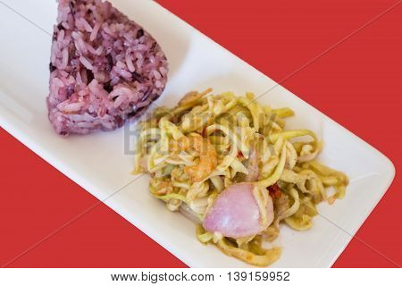 Spicy green mango salad with berry sticky rice stock photo