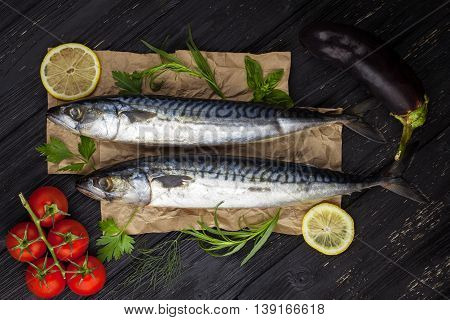 Mackerels served on the black table with lemon, tomatoes, eggplant, and herbs