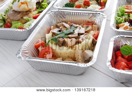 Healthy food and diet concept. Take away of fitness meal. Weight loss nutrition in foil boxes. Couscous with mushrooms at white wood
