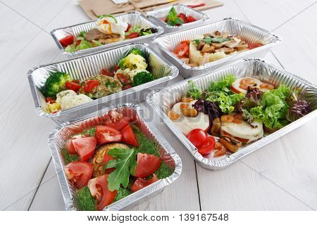 Healthy food and diet concept. Take away of fitness meal. Weight loss nutrition in foil boxes. Vegetables, guacamole, mozarella cheese and other dishes closeup at white wood