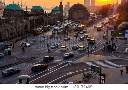 HAMBURG, GERMANY - MARCH 29, 2014: Car traffic in the city center. Aerial view of the port and road junction. Moving people, sunset at the background. Lens flare