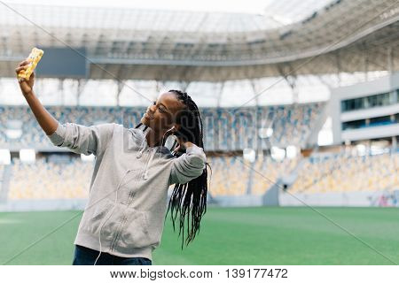 Half length portrait of happy african american woman making selfie at stadium.