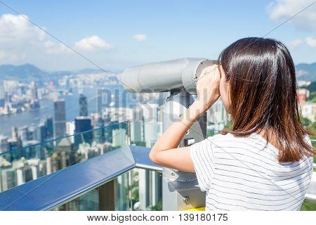 Tourist using binocular looking though Hong Kong skyline