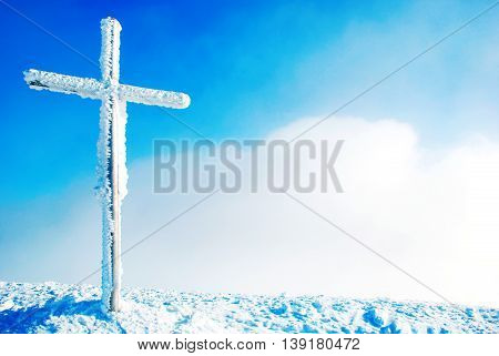 Cross on the top of the mountain in winter. Religion concept
