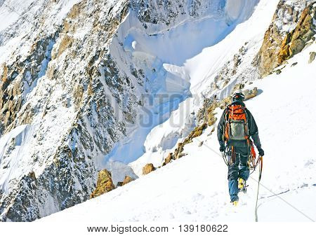 Climber reaches the summit of mountain peak. Climbing and mountaineering sport concept Nepal Himalayas