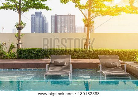 Two beach seats putting on edge of swimming pool with soft orange sunlight on the right corner. Blurry background is tall buildings.