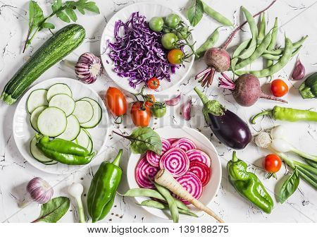 Assortment of fresh vegetables on a light background - zucchini eggplant peppers beets tomatoes green beans red cabbage. Free space for text top view. Cooking background