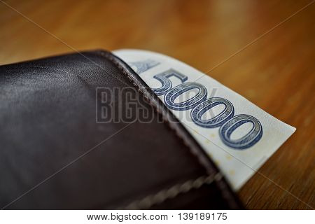Five Thousand Czech Crown (CZK, Kc) bank note hanging accross a leather wallet