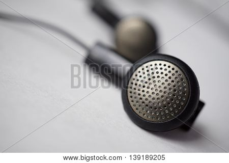 Macro detail of a silver and black perforated headphones (earbuds) with cables