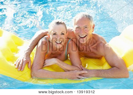 Senior couple having fun in pool poster