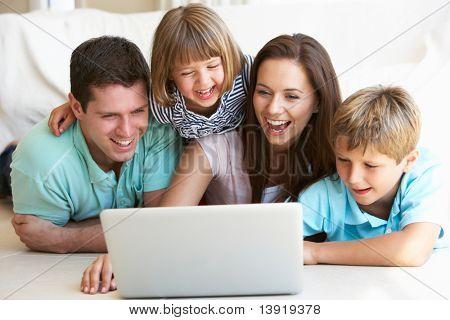 Junge Eltern mit Kindern, auf Laptop-computer