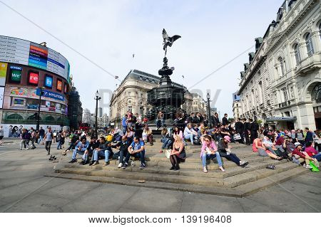 PICCADILLY CIRCUS London - June 06, 2014: People enjoying the sun at Piccadilly Circus London