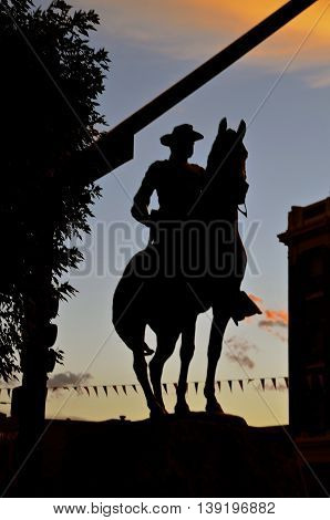 MANDAN, NORTH DAKOTA: July 2, 2016:  A statue of President Theodore Roosevelt on horseback is silhouetted against the sky in the evening sunset.