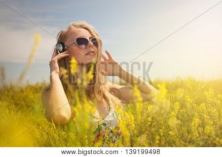 Beautiful Young  Blond Woman With Headphones Outdoors Enjoying Music