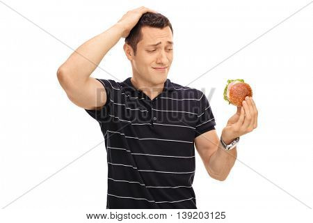 Tempted guy looking at a tasty sandwich isolated on white background