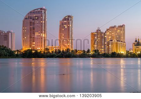 Lightened buildings reflected in river water. Evening city. HDR