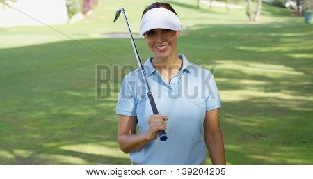 Smiling friendly woman golfer walking on a course