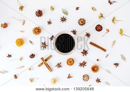 coffee mug with cinnamon cardamom and dry seasonal flowers. Flat lay top view