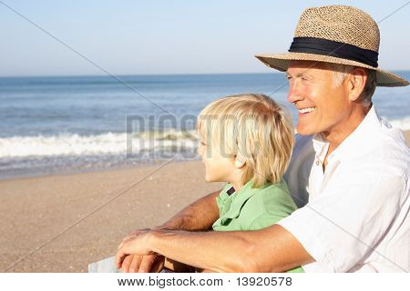 Grandfather with child on beach relaxing