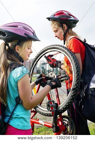 Bikes bicyclist girl. Children girls wearing bicycle helmet with hand pump for bicycle. Girl pump up bicycle tire. Children bicycle repair.