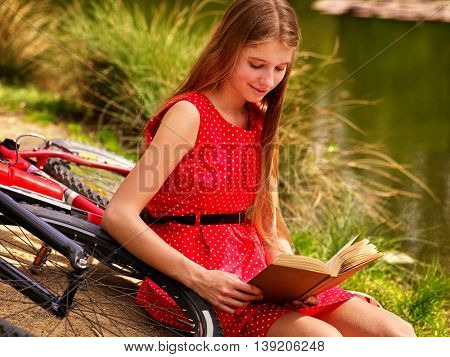 Girl wearing red dress read book on beach of river. Girl arrived on bicycle. Girl leaning near bicycle on river beach in park outdoor.