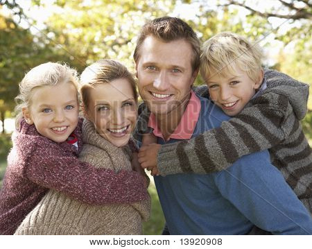 Young family pose in park