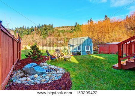 Fenced Back Yard With Blue Barn Shed.