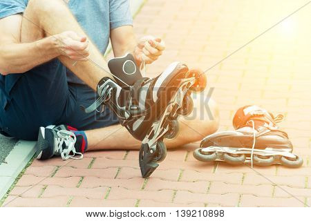 Man preparing for roller blading, putting on rollerblades.