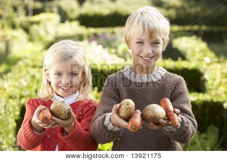 Young children in garden pose with vegetables