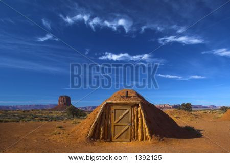 Hogan the traditional Navajo red clay earth house with backdrop of famous table mountains of the Navajo National monument on the background poster