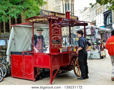 CAMBRIDGE UNITED KINGDOM - JULY 18 2011: Student talking to a vendor at a traditional hot dog stand.