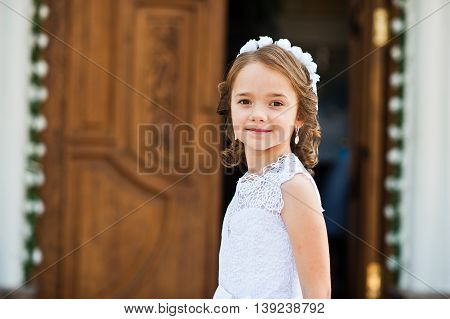Portrait Of Cute Little Girl On White Dress And Wreath On First Holy Communion Background Church Gat