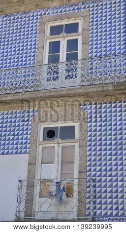 Facade of house decorated on blue and white tiles in Guimaraes Portugal.
