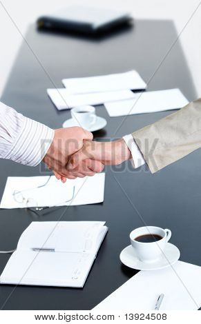 Image of business people shaking hands over workplace