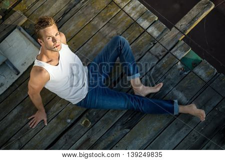 Brutal barefoot guy lies on the wooden surface outdoors. He wears a white singlet and blue jeans and looks into the camera while smokes a cigarette. Photographed from the upper point. Horizontal.