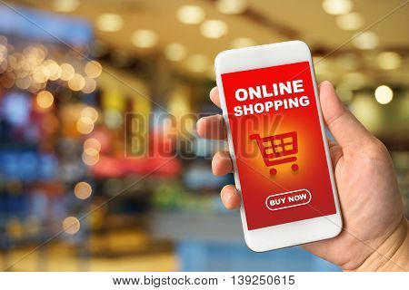 Woman hand holding smartphone against blur bokeh of shop background with word online shopping buy now