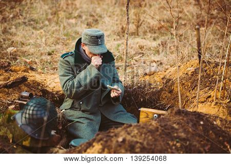 Pribor, Belarus - April, 04, 2015: Unidentified Re-enactor Dressed As World War German Wehrmacht Soldier In A Trench Settling For Night