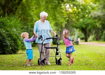Happy senior lady with a walker holding hands of little boy and girl. Grandmother with grand children enjoy a walk in summer park. Kids supporting disabled grandparent. poster