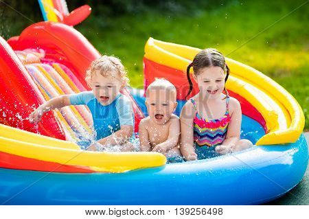 Children playing in inflatable baby pool. Kids swim and splash in colorful garden play center. Happy boy girl and baby with water toys on hot summer day. Family having fun outdoors in the backyard.