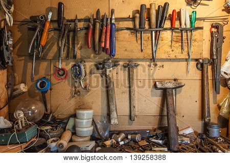 Tools on the wall and table to keep hammers wrenches ring spanners hammer pliers screwdrivers monkey wrenches screws bolts adjustable wrench insulating tape and other do-it-yourself (DIY) tools