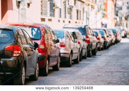 Cars Parked On Street In European City In Sunny Summer Day. Background