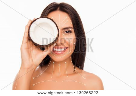 Cheerful Smiling Pretty Young Woman Holdind Coconut Near Her Face With Arrows
