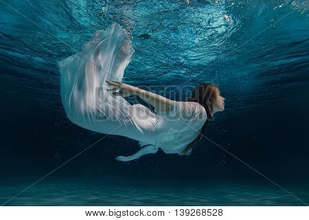 Woman in white dress swimming under water like a mermaid amid bursts.
