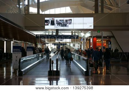 LOS ANGELES, UNITED STATES - DECEMBER 28: Travelers go on and next off the flat escalator of a departure terminal at LAX on December 28 2015 Los Angeles.