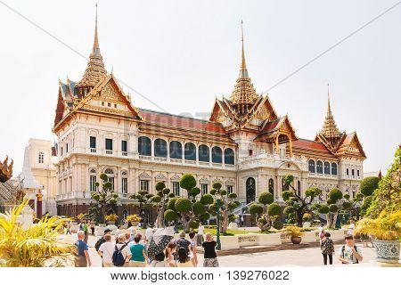 BANGKOK THAILAND - January 19 2011. Tourists walk in Royal Palace Bangkok Thailand. Large groups of people visit famous architecture landmark.