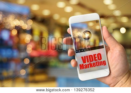 Woman hand holding smartphone against blur bokeh of shop background VIDEO Marketing concept