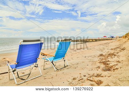 A day at Edisto Beach in South Carolina with vacationers marking their area with beach chairs, umbrellas, etc.